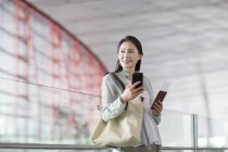 Chinese woman holding smartphone and ticket at airport — Stock Photo