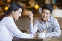 Chinesischer Mann und Frau mit digital-Tablette im café — Stockfoto