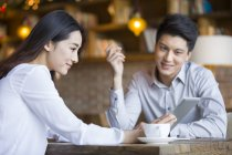 Chinese man and woman using digital tablet in cafe — Stock Photo