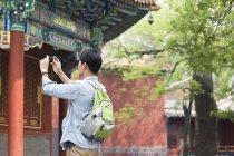 Uomo cinese che scatta foto con smartphone nel Tempio di Lama — Foto stock