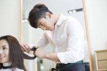 Chinese barber cutting female customer hair — Stock Photo