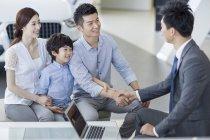 Família chinesa, agitando as mãos com o vendedor de carro no showroom — Fotografia de Stock