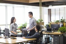 Chinese co-workers talking in office — Stock Photo