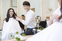 Chinesische Barbier mit weiblichen Kunden in Spiegel — Stockfoto