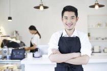 Café-restaurant chinois propriétaire debout avec les bras pliés — Photo de stock