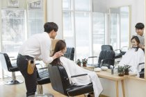 Китайский парикмахер говорить клиенту в салоне волосы — стоковое фото