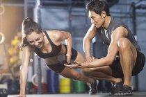 Китаянка отжимается с тренером в спортзале — стоковое фото