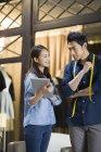 Stilisti di moda cinese utilizzando la tavoletta digitale in studio — Foto stock