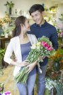 Chinese couple buying flowers in store — Stock Photo