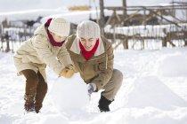 Китайский отец и сын подвижного снежный ком вместе — стоковое фото