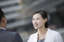 Chinese businesswoman talking with man on street — Stock Photo