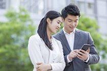 Китайские коллеги используют смартфон на улице — стоковое фото