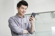 Hombre de negocios chino usando teléfono inteligente en la oficina - foto de stock