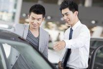 Coche chino distribuidor ayudando a elegir del cliente coche en showroom - foto de stock