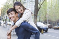 Chinois homme tenant cochon retour copine sur la rue — Photo de stock