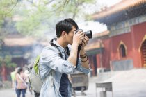 Turista chino tomando fotos en el Templo Lama - foto de stock