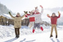 Chinese children jumping in snow — Stock Photo