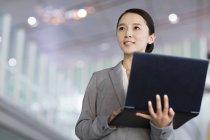 Empresária chinesa de pé com laptop dentro de casa — Fotografia de Stock