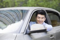 Chinese man sitting in car and looking in camera — Stock Photo