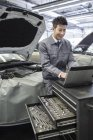 Chinese auto mechanic using laptop in repair shop — Stock Photo