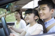 Chinese couple with daughter sitting in car — Stock Photo