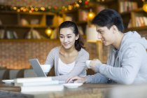 Étudiants chinois à l'aide de portable au café-restaurant — Photo de stock
