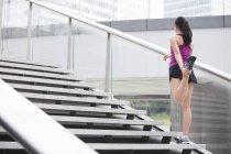 Femme chinoise étirant la jambe sur les escaliers — Photo de stock