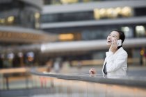 Chinese businesswoman talking on phone in financial district — Stock Photo