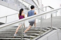 Chinese couple stretching legs on stairs — Stock Photo