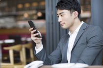 Chinese man using smartphone in restaurant — Stock Photo