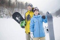 Couple chinois de surfeurs des neiges debout sur pente — Photo de stock