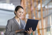 Chinesische Geschäftsfrau mit Laptop im Haus — Stockfoto