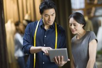 Chinesische Mode-Designer und Kunden digitale Tablet im Shop betrachten — Stockfoto