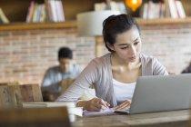 Étudiante chinoise étudie avec ordinateur portable au café — Photo de stock