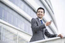 Chinese businessman standing in front of office building with smartphone — Stock Photo