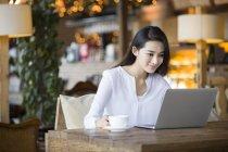 Femme chinoise utilisant l'ordinateur portable au café — Photo de stock