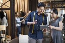 Chinesische Mode-Designer und Kunden suchen bei digital-Tablette — Stockfoto