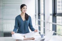 Femme chinoise pratiquant le yoga sur la table de bureau — Photo de stock