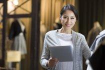 Владелец китайского магазина одежды стоит с цифровым планшетом — стоковое фото