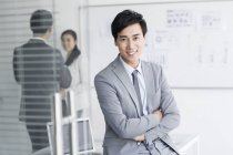 Chinese businessman sitting with arms folded — Stock Photo