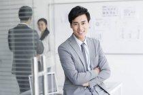 Китайский бизнесмен сидит со сложенными руками — стоковое фото