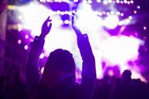 Mujer con brazos levantados en el festival de música - foto de stock