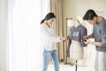Chinese fashion designers working with mannequin — Stock Photo