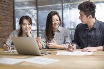 Chinese co-workers sitting at meeting room with laptop — Stock Photo