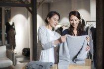 Maduro chinês boutique proprietário ajudando cliente escolher roupas — Fotografia de Stock
