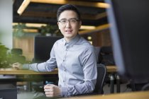 Chinese male IT worker sitting at workplace — Stock Photo
