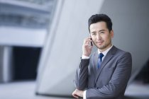 Chinese businessman talking on phone and looking at view — Stock Photo