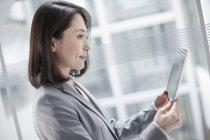 Китайская предпринимательница с помощью цифрового планшета — стоковое фото