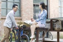 Chinese woman sitting on bench with coffee and talking to man with bike — Stock Photo