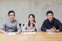 Китайские ИТ-работники сидят в зале заседаний и смотрят в камеру — стоковое фото